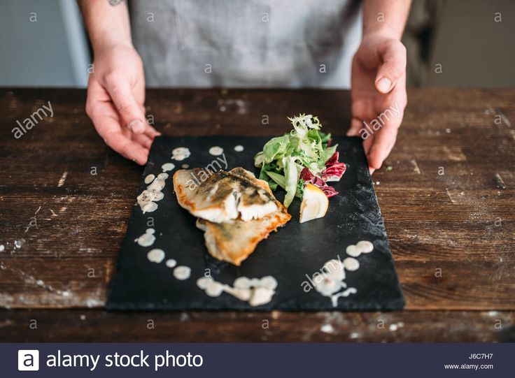 Chef decorate with vegetables dish of fried fish on wooden tray. Fresh healthy seafood. Gourmet dinner Stock Photo