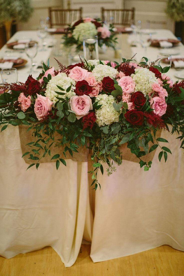 Head Table Floral Arrangement to include Pink O'Hara garden roses, Black Magic burgundy roses, astilbe, astrantia, spray roses, white hydrangea and mixed foliage. Flowers by Janie- Calgary Wedding Florist Photo: http://cednaphotography.com Planning: @mountainbride