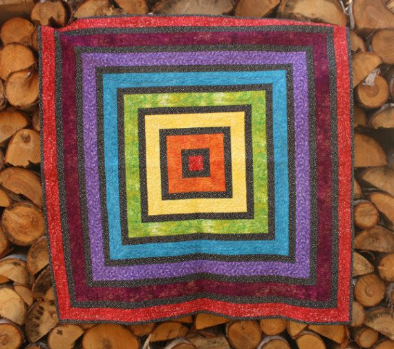 """The Rainbow Ripple (44"""" x 44"""") is a perfect wall quilt or baby quilt. It is beautifully machine quilted and the bright colours are vibrant against the black stripes."""