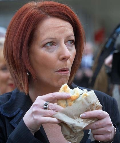 In this article - Ex Prime Minister of Australia Julia Gillard eating a pie and her thoughts on the 2010 Federal Election issue: Should tomato sauce be provided free with meat pies?