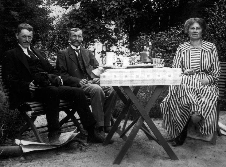 Två herrar och en dam intager stillsamt sitt eftermiddagskaffe i trädgården en dag år 1937. / Two gentlemen and a lady enjoying a tranquil afternoon coffee in the garden sometime in 1937.  Foto: Birger Andersson, Svartsbo Ref.nr: XLM_B 2251