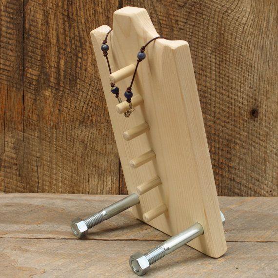Ein Kettendisplay, das aus einem Frühstücksbrettchen, einigen Holzdübeln und zwei gr0ßen Schrauben mit Muttern gefertigt wird. Gesehen bei etsy.