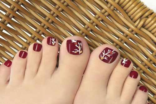 Pretty pedicure for Fall: Maroon polish with a White tree and a couple of Yellow and Brown  dots.