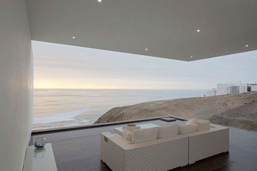 Casa VU is a minimalist house located in Lima, Peru, designed by TDC. The project is set on a cliff with a steep slope and a privileged view to an isle on the sea. Every room tends to open up to this natural surrounding through overlapped volumetries which generate shadows and open spaces such as the terrace which ends up becoming a contemplation space. At this house, architecture and structure merged in order to create two white volumes (un-gravitational) set over two earthly volumes…