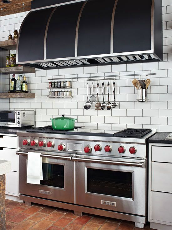 Keep Essentials Handy. Make food prep easy by storing items off the counter but within reach. Here, a thin strip of stainless steel artfully organizes spices, utensils, and other cooking essentials. Open shelves flank the range to keep larger cooking items and dishes on hand, as well.