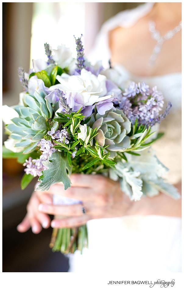 The bride will carry a small bouquet of green succulents, lavender, rosemary, sage, white heather, ivory garden roses, and seasonal greenery wrapped in burlap ribbon with the stems showing.