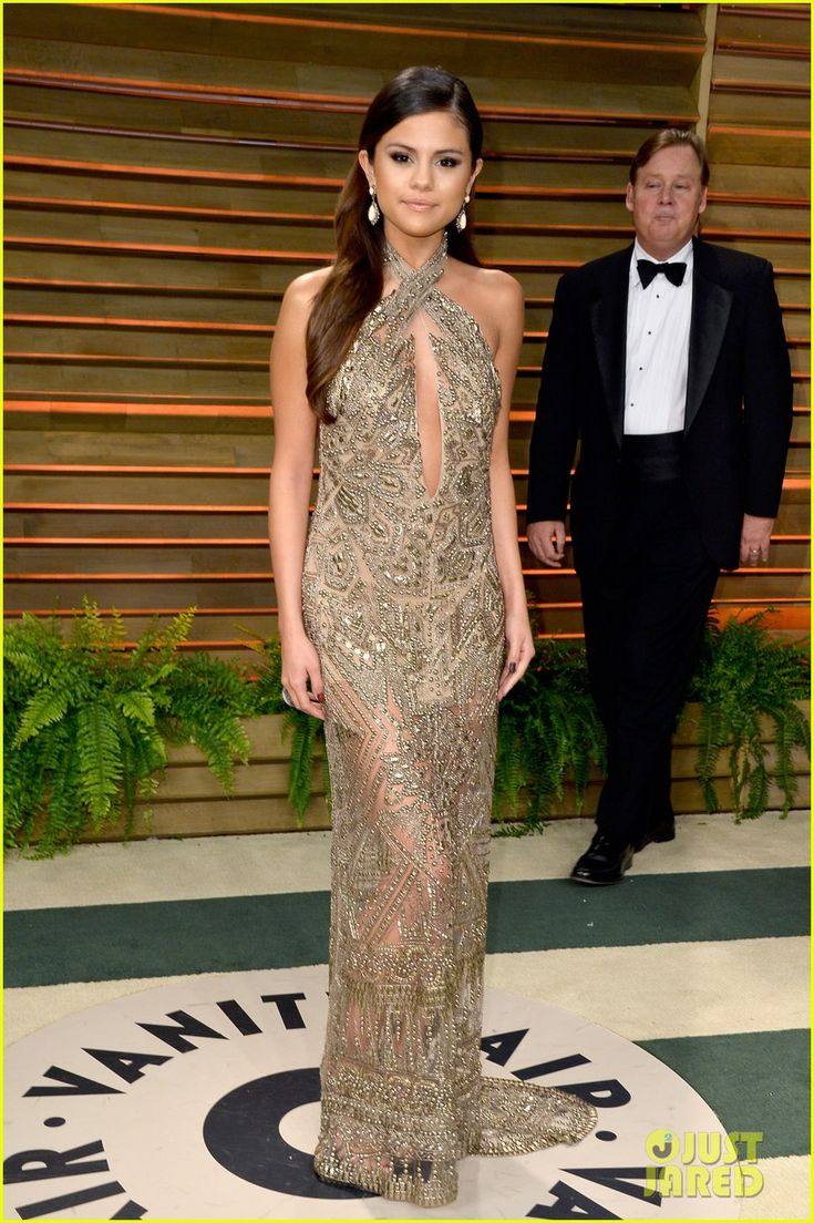 Selena Gomez: GOLDEN at the Vanity Fair Oscars Party 2014! The 21-year-old starlet wore a beautiful Emilio Pucci gold embroidered tulle halter neck gown from the Fall/Winter 2014-15 collection.