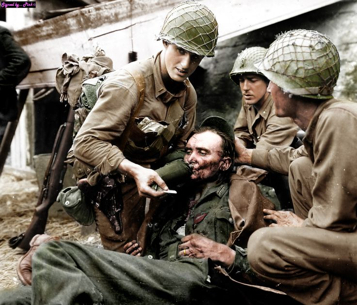 American soldiers helped the wounded German soldier. German soldier seriously wounded in the chest and head – riddled by shrapnel from artillery mines. Battle of Normandy,...