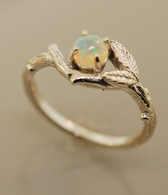 Two leaves are added to a delicate budding branch that showcases a 5 mm Wello Opal. It is all sterling silver. A great ring for those that love