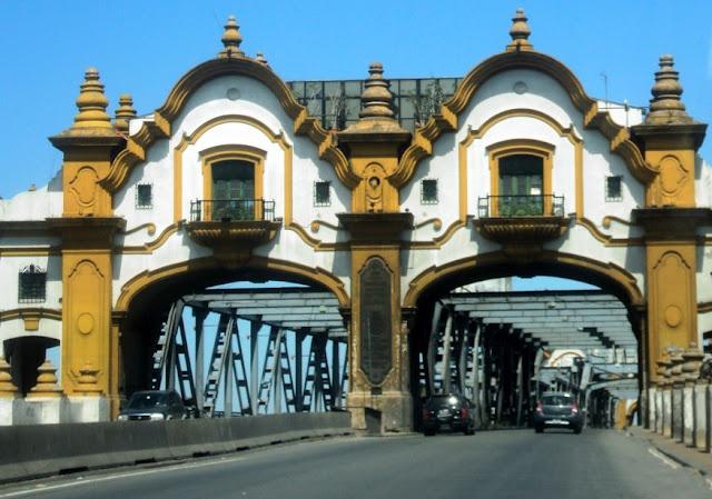 Puente Alsina,construido en 1938, el Puente Alsina (durante un tiempo conocido como Puente Teniente General Uriburu, debido al presidente argentino del mismo nombre), se ubica en el Riachuelo de Buenos Aires. Tiene origen en un puente previo construido por Enrique Ochoa en el conocido como Paso de Burgos, que databa de 1855, y que fue arrasado por una riada ese mismo año; asimismo, en 1856 se construyó otro que tampoco duró más de un año.