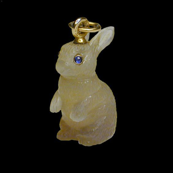 Fabergé miniature rabbit, late 19th century. Agate, with finely carved fur and cabochon sapphire eyes. Suspended on a yellow gold ring bearing the marks for Fabergé. First of two photos.