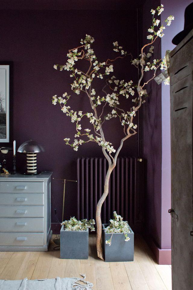 Une vraie branche sur laquelle ont été attaché avec du fil de fer ton sur ton très fin de petites fleurs en tissu.