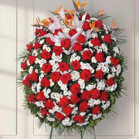 Corona de flores compuesta por Crisantemo blanco, Clavel blanco, Rosas rojas abiertas. Envíos de plantas y flores a domicilio.