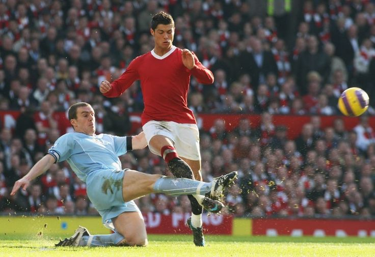 Richard Dunne tackles Cristiano Ronaldo of Manchester United.