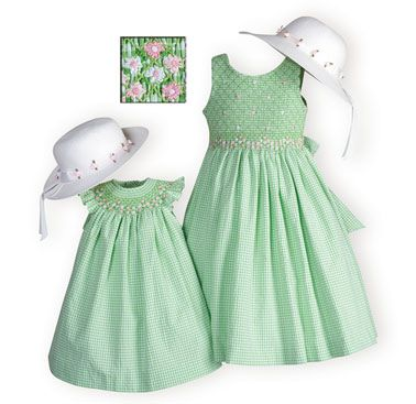 Green and white gingham checked dresses of cotton/poly seersucker. Hand-smocked bodices with pink and white floral embroidery. Knee lengths. Machine w