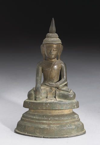 A Burmese bronze figure of Buddha Shan State, 16th/17th Century Seated in meditation with his hands in the bhumisparsa mudra, the crisply cast facial features framed by a simple coiffure of small curls surmounted by a large flame finial, all supported on a waisted triangular plinth. 9 1/4in (23.5cm) high