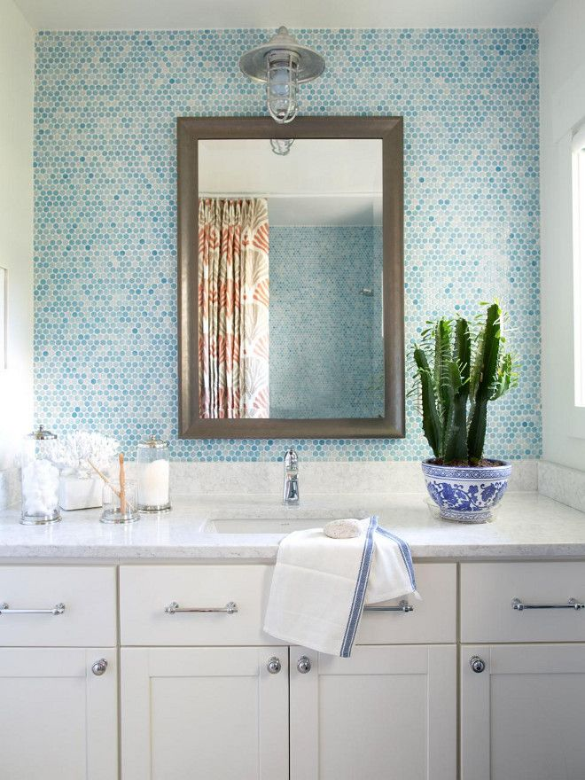 In this coastal-inspired bathroom, a handsome framed mirror creates a focal point behind the vanity, and contrast for the surrounding blue tiles and white ...