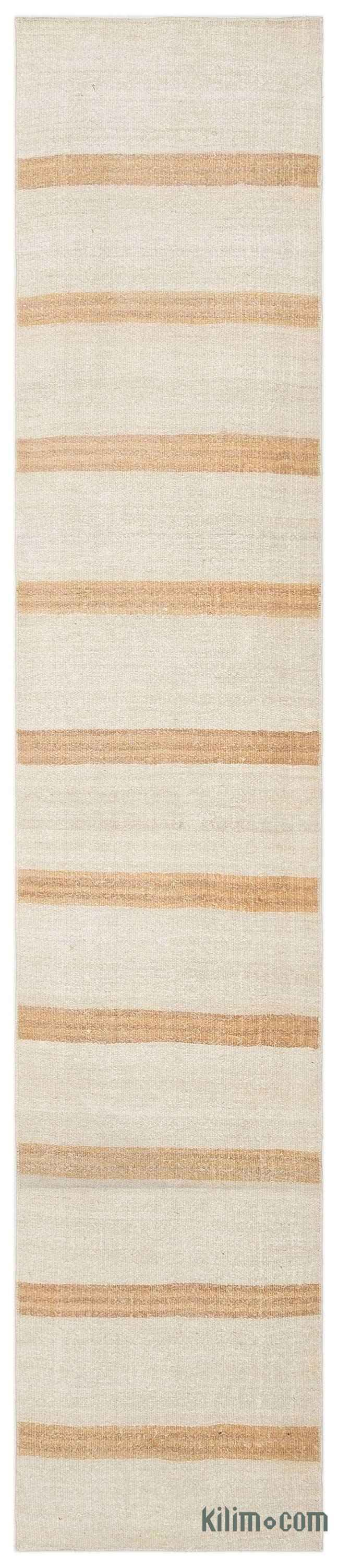 Vintage kilim rug handwoven in Turkey with hemp fiber. Turkish villagers produced hemp stalk until the 1960's when its production was prohibited together with its cousin, medical cannabis. These Anatolian rugs with modern appeal were mostly woven for drying fruits, to store wheat or as floor covers. This minimalistic beige rug measures 10'1'' x 2' (307 cm x 61 cm).We professionally clean all our vintage rugs, but stains are a reminder of the rugs' history.