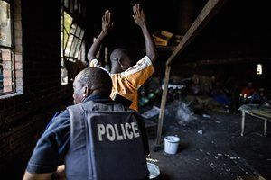 A man holds up his hands as a South African riot officer raids the kitchen of a hostel in Benoni. Local residents are suspected of having acted against foreign-owned shops in the area, throwing stones at the trucks bringing in stock and forcing them to shut down. South African president Jacob Zuma appealed for calm as an eruption of xenophobic violence spread to Johannesburg, raising fears that the country's dire economic troubles could spark widespread unrest