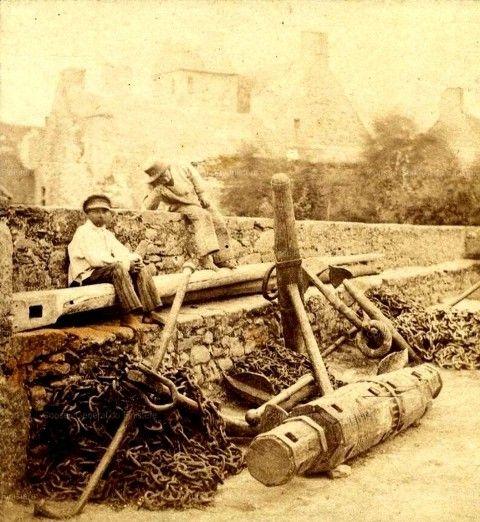 Guindeau en bois cerclé de fer,  une vieille ancres à jas de bois aux extrémités de section ronde et des ancres en fer. Toute l'atmosphère de l'ancien cabotage à voiles. Photo 1857, Roscoff.  Brittany