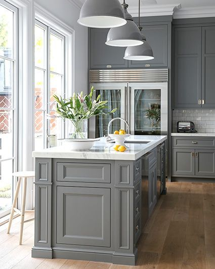 Grey cabinets, glass-door refrigerator , pendant lights over sink flanked by stainless steel dishwasher.