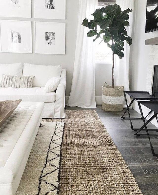Layering a rug under the coffee table adds contrast and a design touch to this white space. Great use of the large basket as a planter.