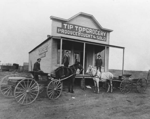 """HISTORIC EARLY DAYS / OKLAHOMA CITY, OK / GROCERY STORES: Proprietors of the Tip Top Grocery had the foresight to anticipate the suburbs of Oklahoma City. In this 1904 photo the store was on a country road at what is now NW 10 and Western. In the wagon is Frank Young; at left on the porch is owner J.S. Kiker. At right is Ben Secor. Published on 04/16/1989 in The Daily Oklahoman in the Special Centennial supplement """"Growth"""" section. Original photo arrived in library on 10/20/1961"""