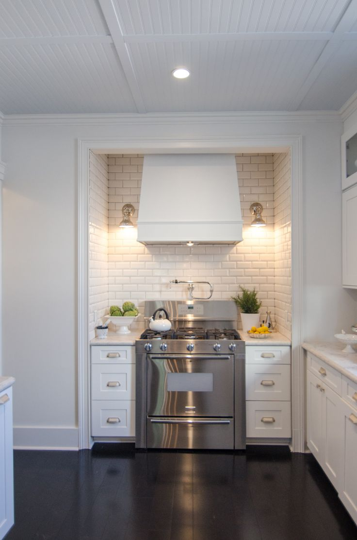 love the stove set in an alcove with sconces, it becomes a focal point in a kitchen, stunning.
