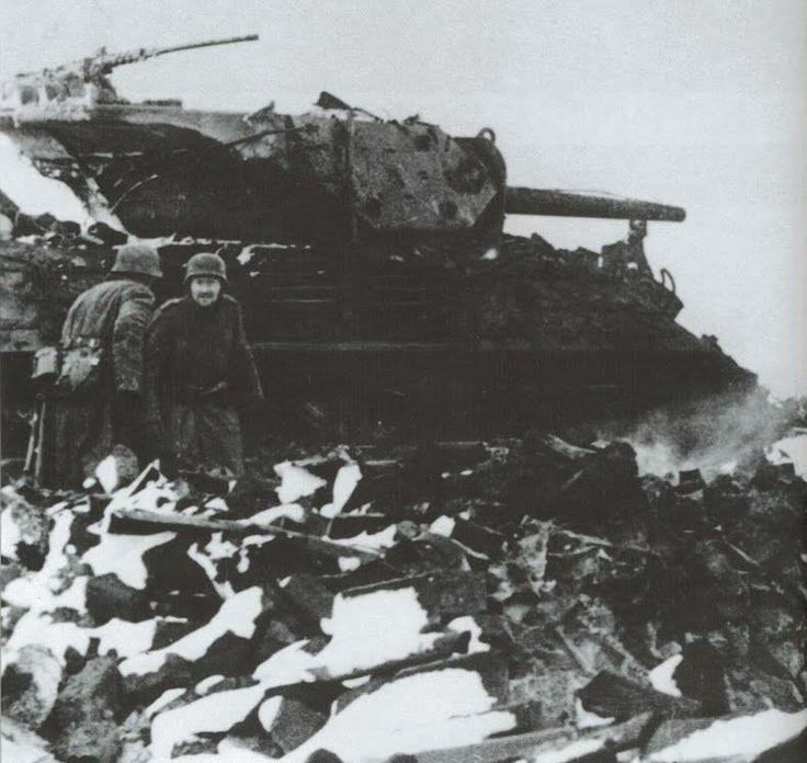 German Soldiers inspect a recently destroyed M-10, American tank hunter, during the Battle of the Bulge in December 1944.