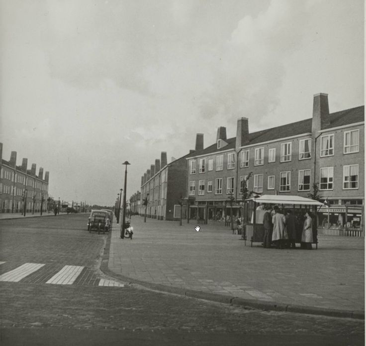 Burgemeester de Fockstraat, eind jaren 50 Een rustige Burgemeester de Fockstraat. Er staan een aantal mensen in de rij voor een haringkar.<br />Fotocollectie Spaarnestad
