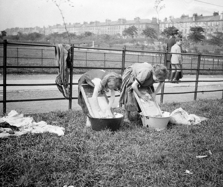 Girls washing laundry in metal basins on Glasgow Green, early 20th century.