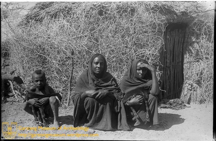 JG-M-A-036 (1912) – Two women and a boy sitting in front of a Tukul house in the village of Begrewiyeh, near Meroë. The boy and one of the women hold a goat each.