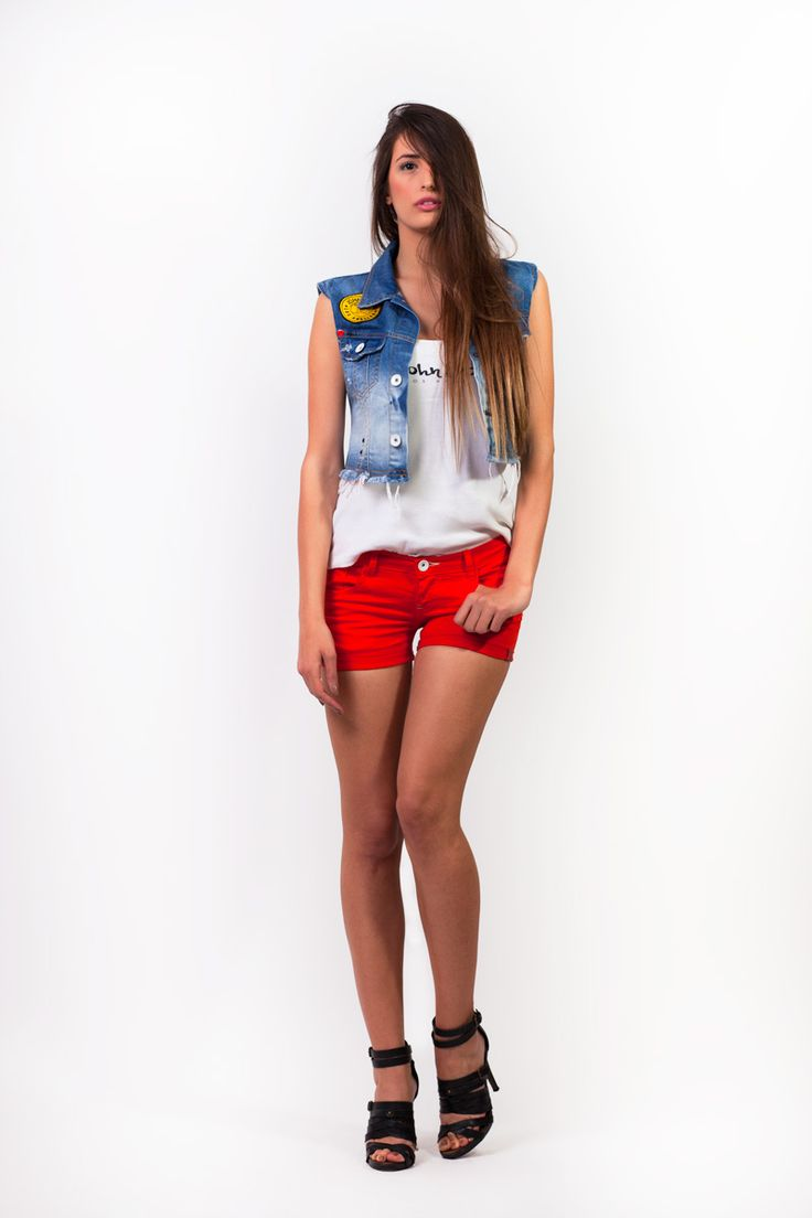 Rock the red shorts with a denim vest