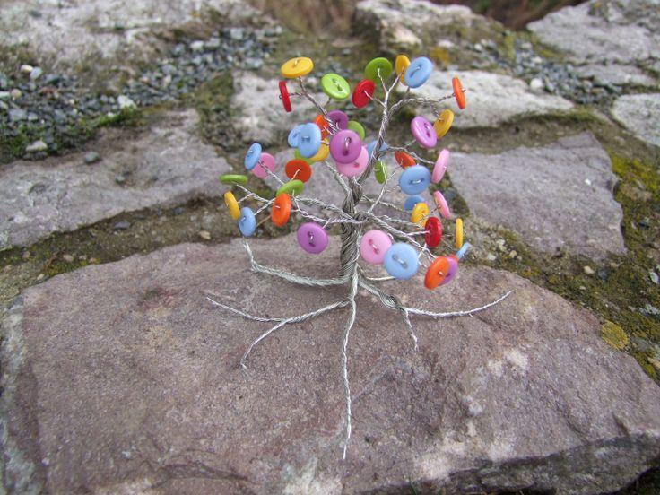 Lentilkový stromeček Krásný lentilkový stromeček je zhotoven z postříbřeného drátku a různobarevných knoflíků. Větvičky se dají tvarovat podle vaší nálady;-) Stromeček je celkově vysoký cca 9 cm. Vhodný jako dekorace do bytu, kanceláře nebo jako dárek.