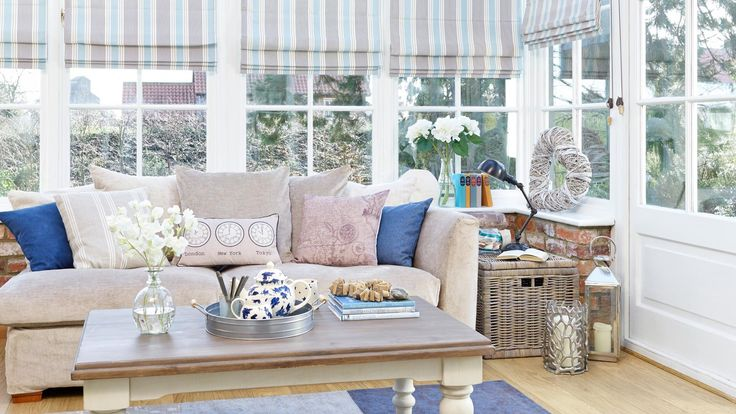 A mix of pale creams and blue tones give this conservatory a washed nautical feel. The painted furniture and neutral sofa are ideal as a backdrop, while deeper-hued rugs and blinds build on the seaside colour theme.