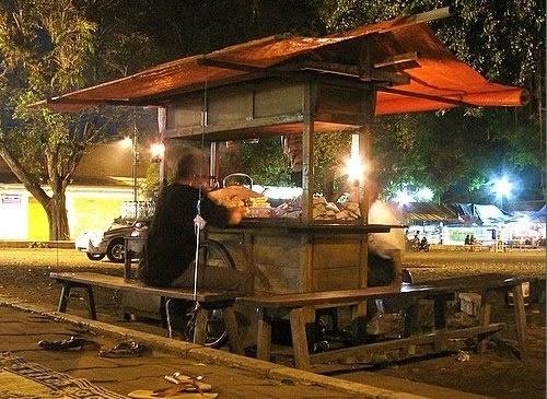 Angkringan, gerobag dorong yang menjual berbagai macam makanan dan minuman di Yogyakarta atau Solo, sudah mulai merambah kota-kota lain, tak terkecuali Jakarta. Di daerah Blok M dan Slipi sudah ada angkringan bergaya Yogyakarta. Gimana sih rasanya makan nasi kucing di angkringan tapi bukan di Yogya? Beda nggak?