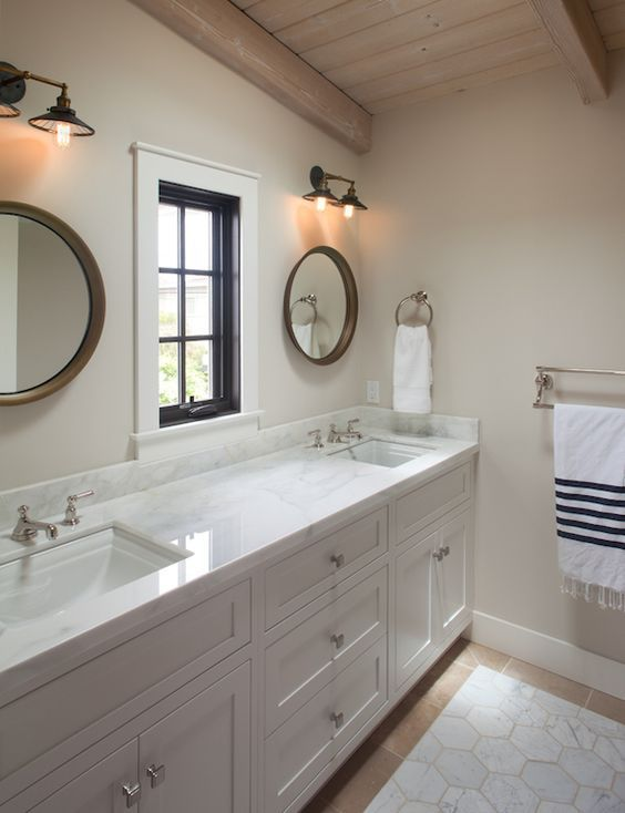 Cottage bathroom features one a rustic plank ceiling over a long custom vanity, divided, into his and her sections adorned with square pulls topped with white marble countertop framing his and her sinks under wood convex mirror illuminated by vintage barn sconces flanking a single window atop a white marble hex inset tiled floor.: