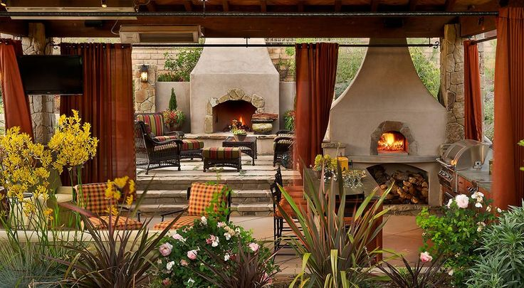 Mediterranean Porch with Outdoor kitchen, Outdoor seating, outdoor pizza oven, exterior stone floors, Fence, Outdoor curtains