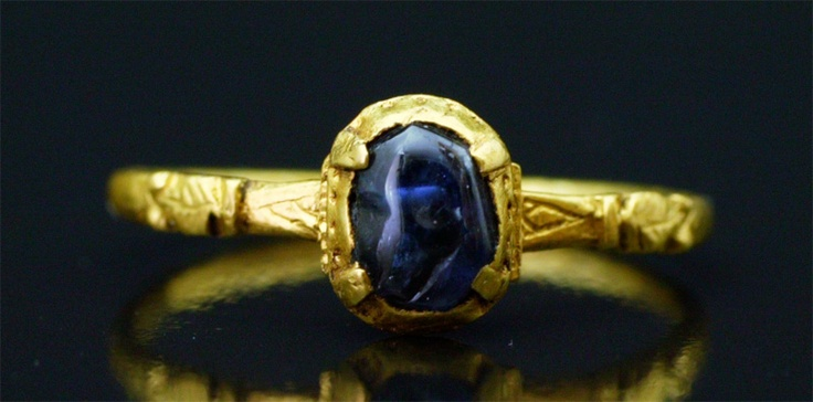 Rare French medieval ring gold (high karat). The box bezel is set with a cabochon-cut sapphire of a beautiful deep color, very probably from the Massif Central (Riou Pezzouliou near Puy en Velay) held by four claws. The hoop is decorated with engraved leaves on the shoulders. France, late 13th century