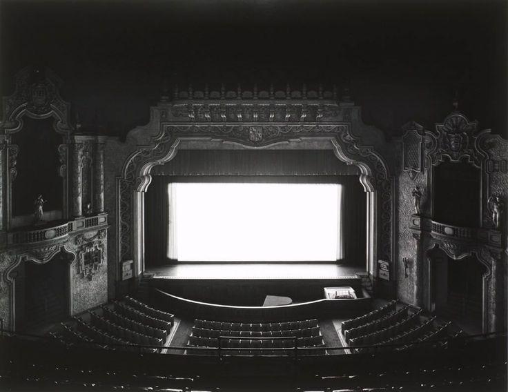 série des cinémas, grande salle vide avec un écran blanc et lumineux, comme si le projecteur était resté allumé à la fin de la séance. En réalité, la salle est pleine de monde et le film se joue. Cette illusion vient du fait que le l'obturateur a été laissé ouvert pendant toute la durée du film. l'appareil a capturétout le film avec les spectateurs dans la salle, mais au final, seul un écran blanc et une salle vide est visible. paradoxe poétique entre vie et mouvement d'un coté