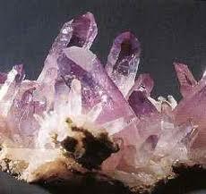 """AMATISTA: Variedad de cuarzo de color violeta más o menos   intenso, en función de la mayor o menor presencia de átomos   de hierro (Fe) intercalados en su estructura cristalina de sílice   (Si02). rro (Fe) intercalados en su estructura cristalina de sílice   (Si02). Su nombre en griego, amethistos, significa  """"lo que   impide la embriaguez"""""""