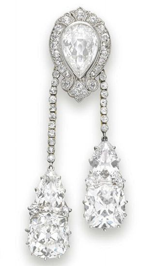 A BELLE EPOQUE DIAMOND LAVALIERE PENDANT   Designed as an old mine-cut diamond scrolled pierced plaque, centering upon a bezel-set pear-shaped diamond, suspending two collet-set diamond tassels each terminating with a pear and cushion-cut diamond, mounted in platinum-topped gold, circa 1900