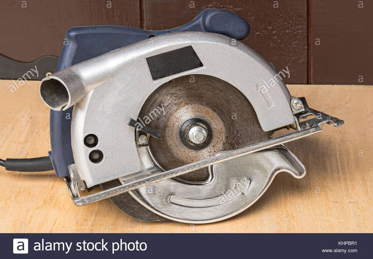 Download this stock image: A small electric circular saw on a workbench. - KHPBR1 from Alamy's library of millions of high resolution stock photos, illustrations and vectors.