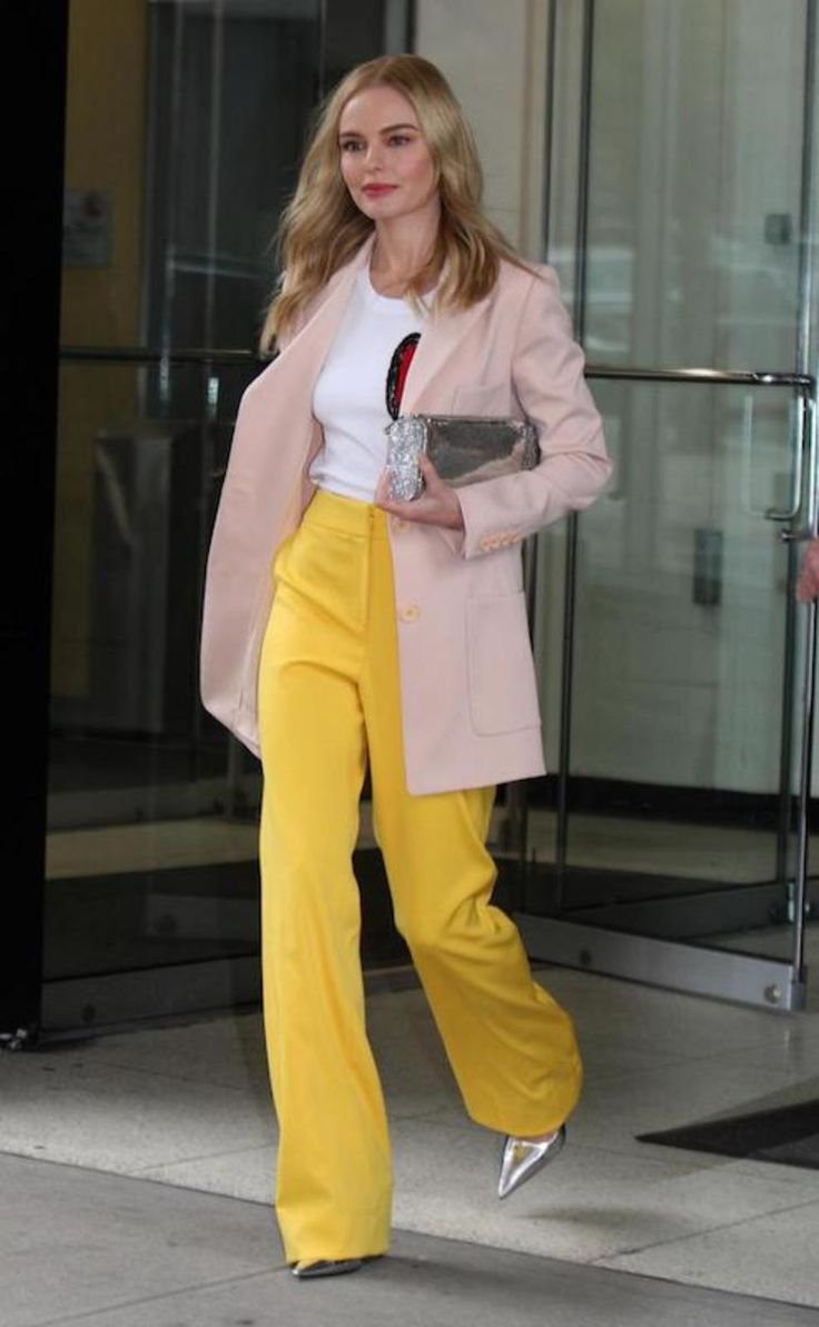 Kate Bosworth wearing a pink blazer coat, white t-shirt with a heart emblem, yellow high-waisted wide-leg trousers, a silver clutch bag, and silver pumps