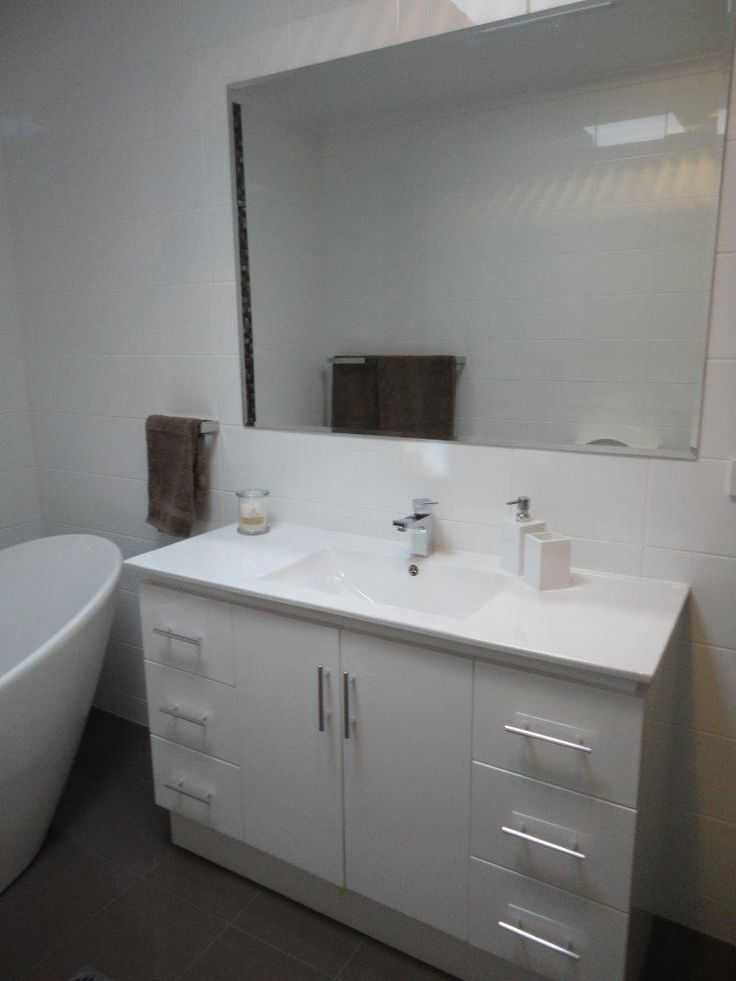 Allign your mirror with the length of your vanity and you can't go wrong! Symmetry and clean lines are key in the bathroom - not to mention getting the tiles right!