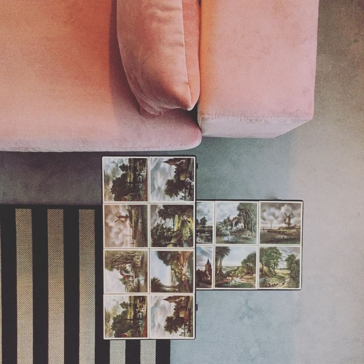 velvet pink couch, nice score second hand tiles table, striped rug with concrete floor