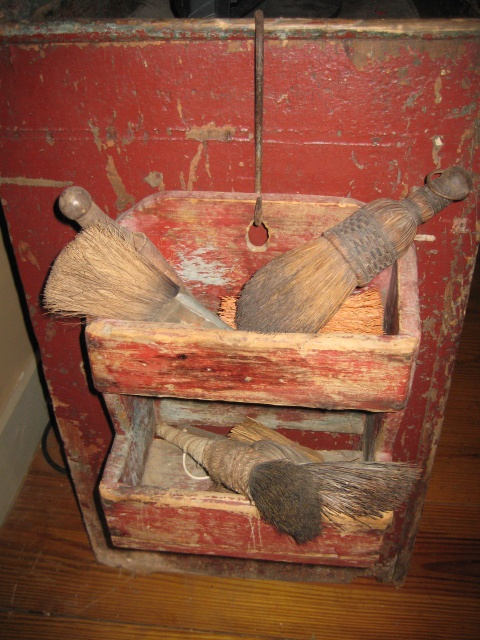 2 tiered prim red box holding a variety of old brooms and brushes...