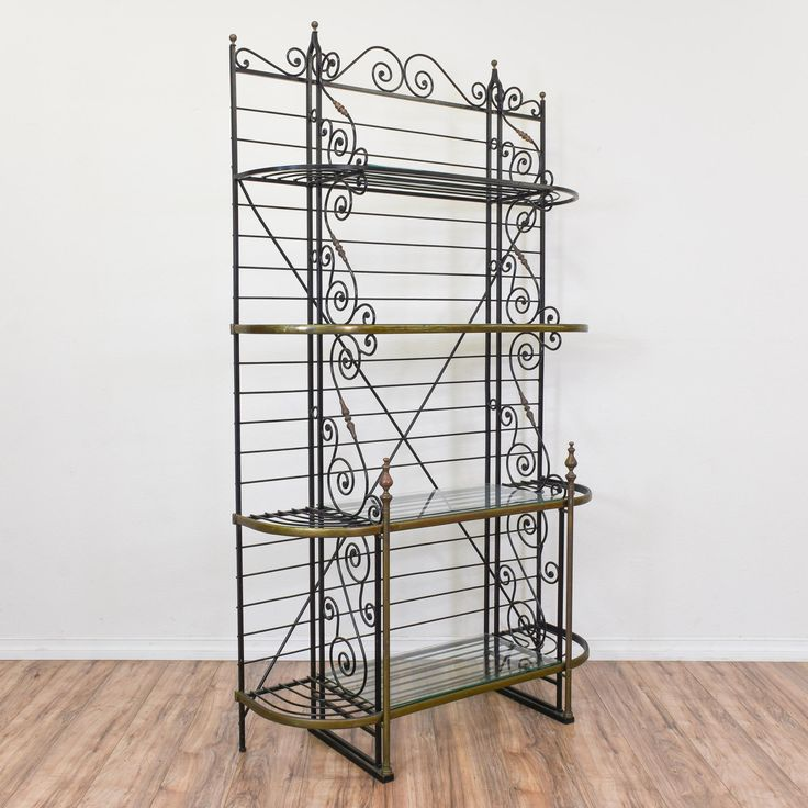 This tall bakers rack is featured in a wrought iron with a black finish and swirl details. This bookshelf is in great condition with 4 shelves, curved brass accents and glass tiers. Perfect for storing snacks and cookbooks!  #mediterranean #storage #bookcase&shelving #sandiegovintage #vintagefurniture