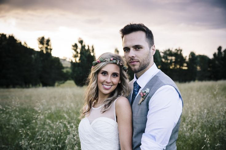 Bride and groom portrait at sunset, flower crown and soft romantic curls for hairstyle