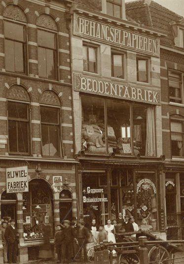 Gezicht op de voorgevel huis Twijnstraat 2 (Nederlandsche Bedden- en Matrassenfabriek - Goedkoope Behangerswinkel) te Utrecht met links een gedeelte van het huis Oudegracht Tolsteegzijde 230.(nu Oudegracht 390) ca 1910